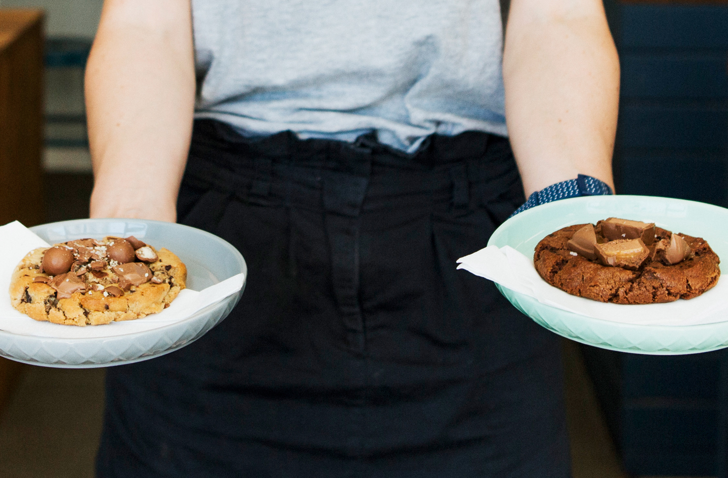 A waitress holds a plate in each hand with a housemade cookie on each.
