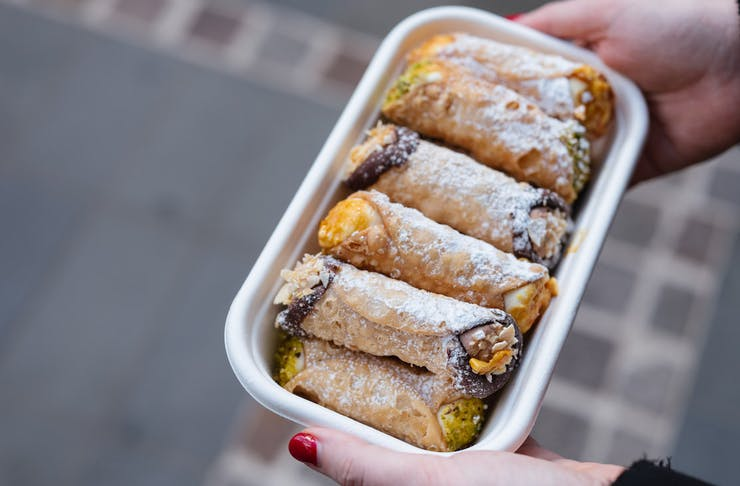 person holds tray of cannoli