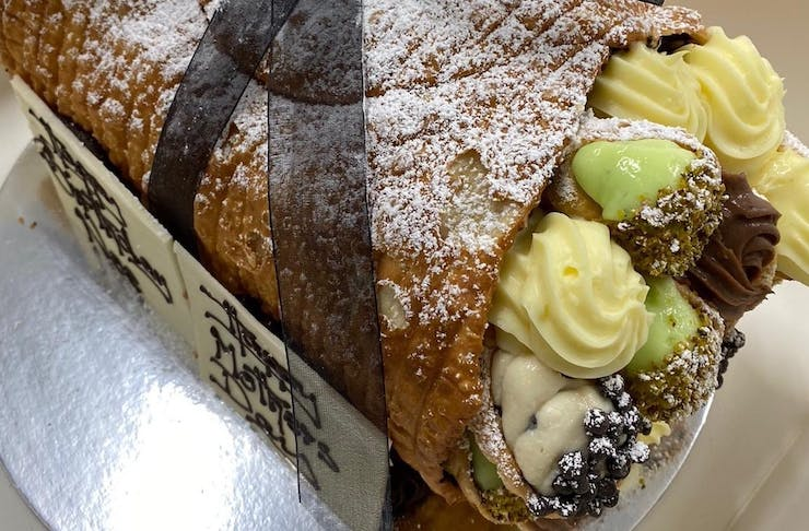 A giant cannoli shell filled with mini cannoli