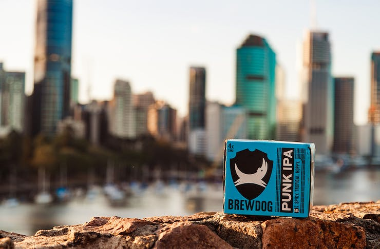 Carton of BrewDog Beer sitting on the Kangaroo Point Cliffs, with the Brisbane City skyline in background.