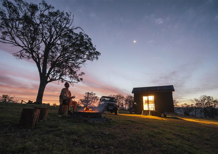 dusk shot of the tiny house, with a person by a campfire outfront