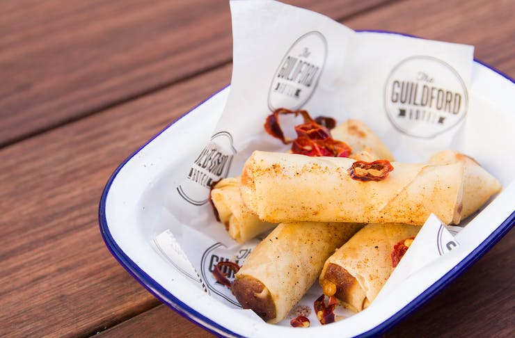 4 cheeseburger spring rolls in a bowl on top of a wooden table top.