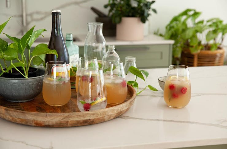 a table laid with cocktails, a plant and glass jars.