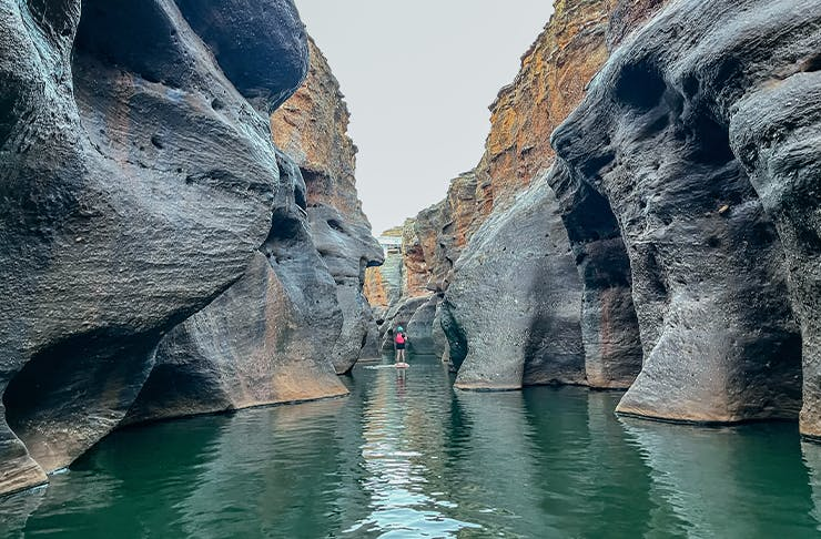 a person on a SUP in a deep gorge