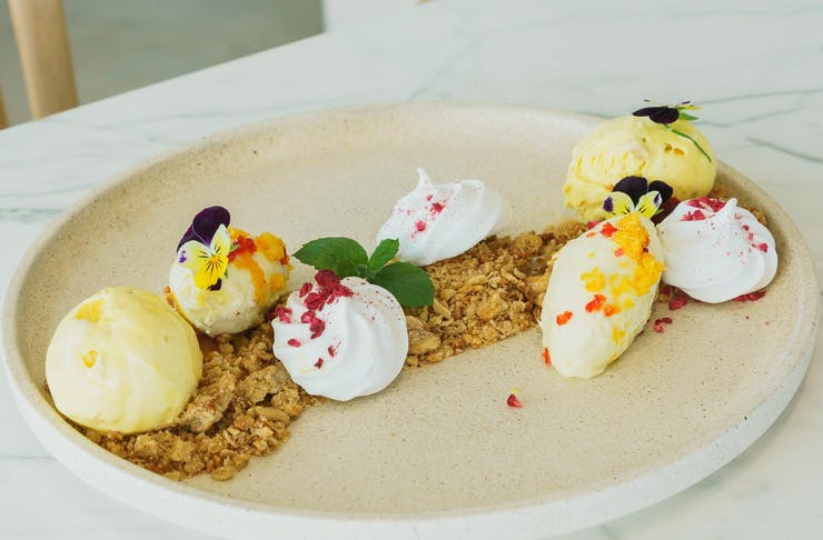 Plat of deconstructed pavlova with biscuit crumbs and ice cream on a white marble table.