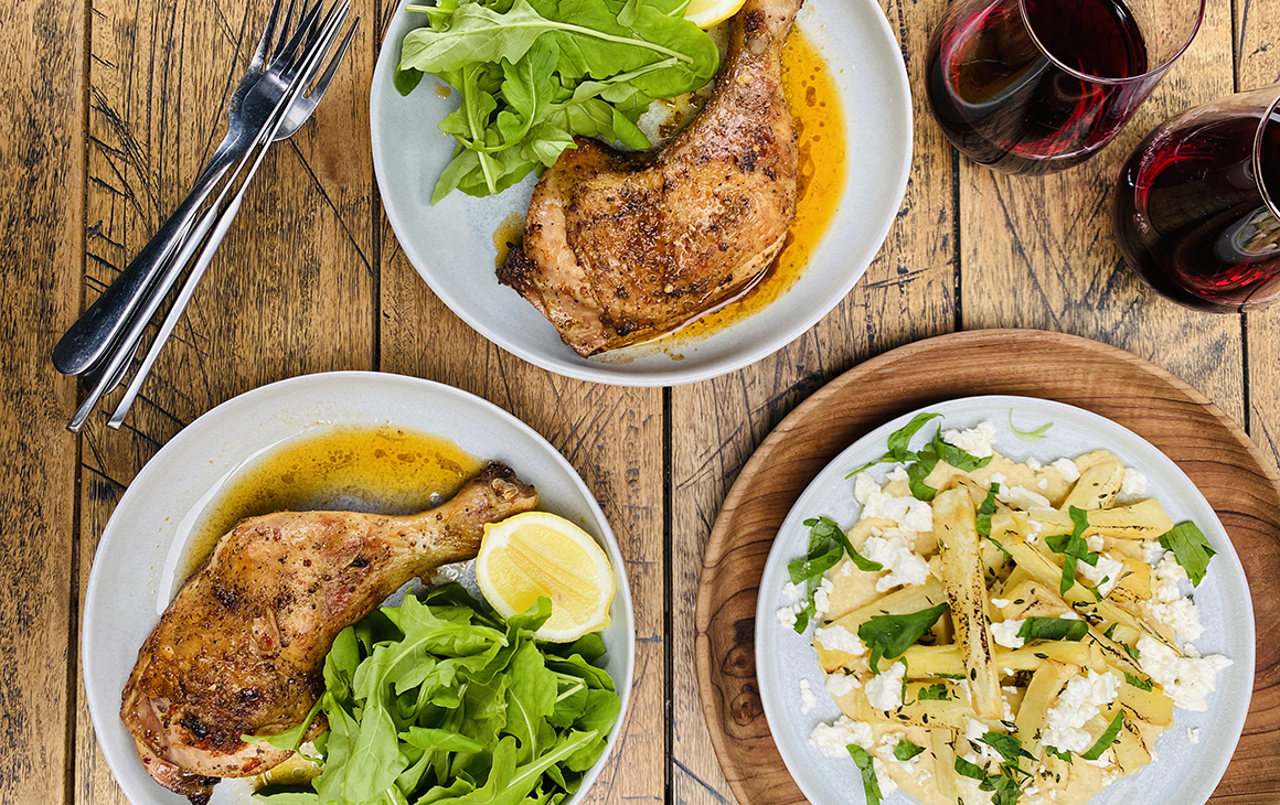 Chicken maryland with lemon garlic and pimento dela vera, roasted parsnip with feta hummus and rocket sits on a plate with a couple of glasses of red wine.