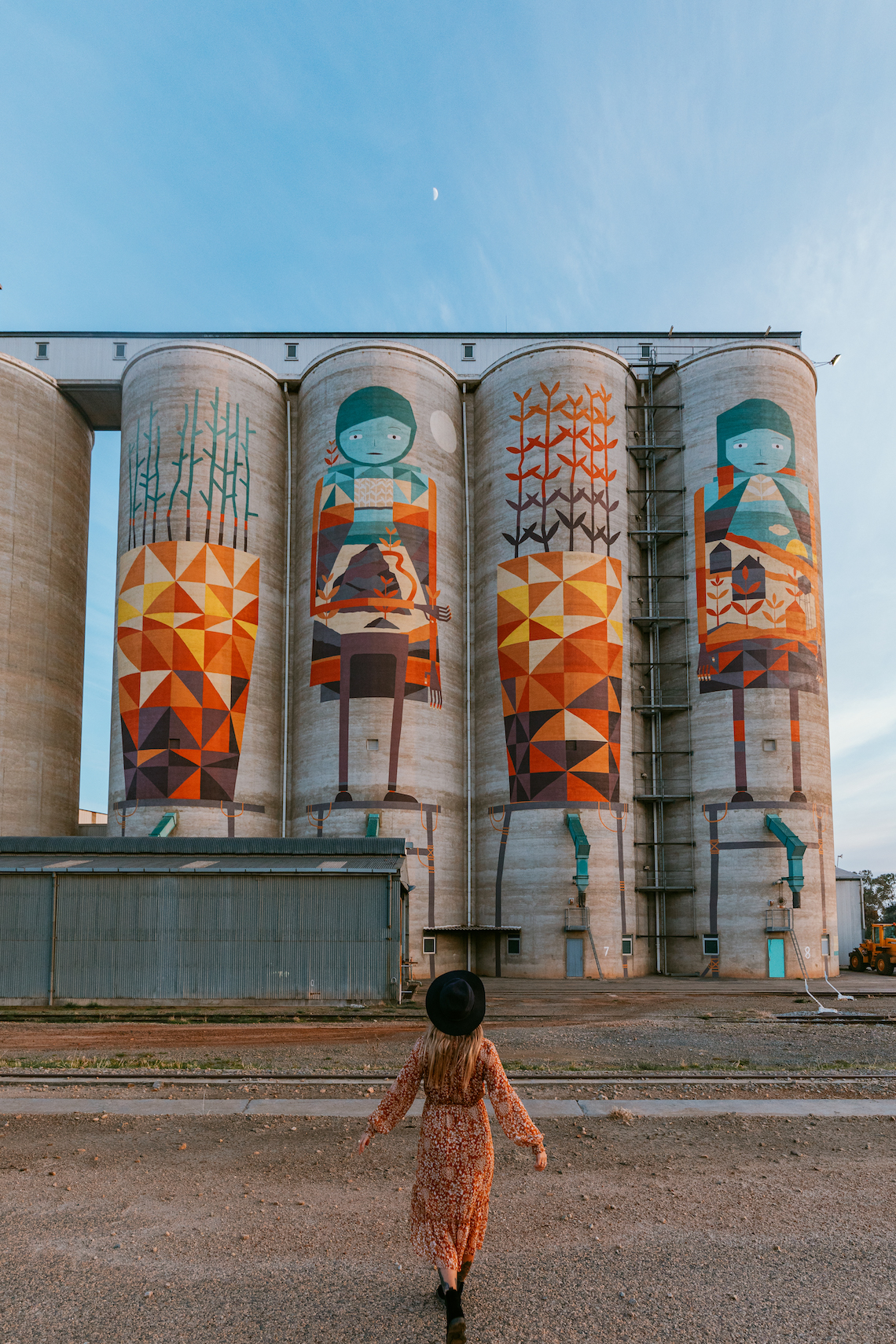 Woman in red dress standing in front of Merredin silos