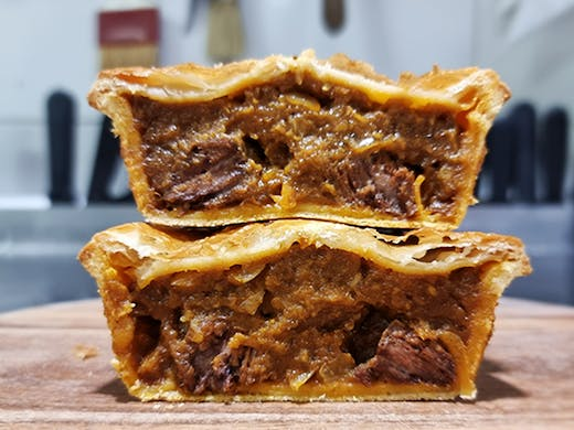 Two pies that have been sliced open showing the chunky beef filing and golden pastry.