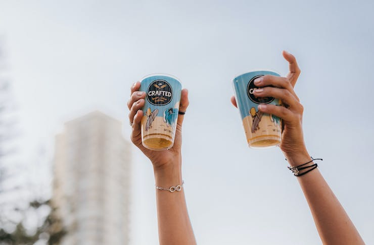 Two hands holding two Crafted Beer & Cider Festival cups against the blue sky.
