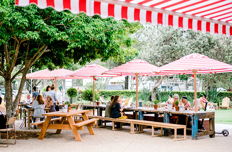 Picnic tables under red and white striped umbrellas are filled with locals at Gold Coast cafe, Custard Canteen.