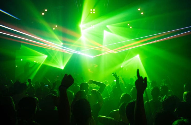 the silhouette of a crowd at a music concert with green laser lights
