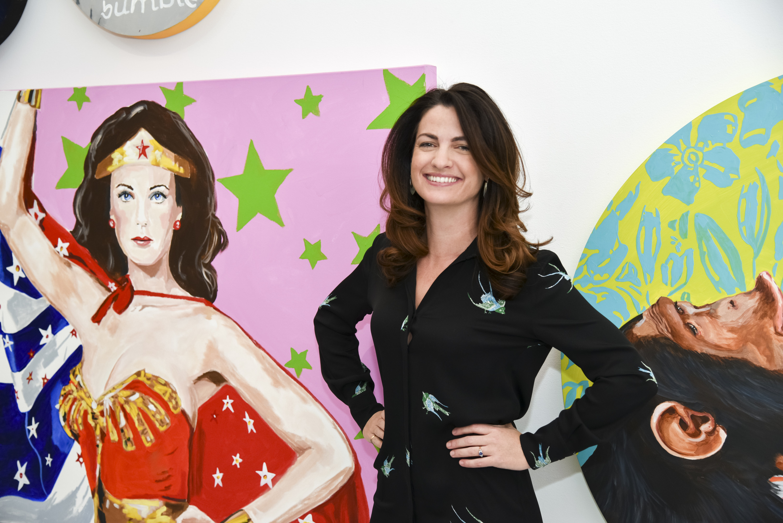 Meggie Palmer stands next to a wonder woman mural.