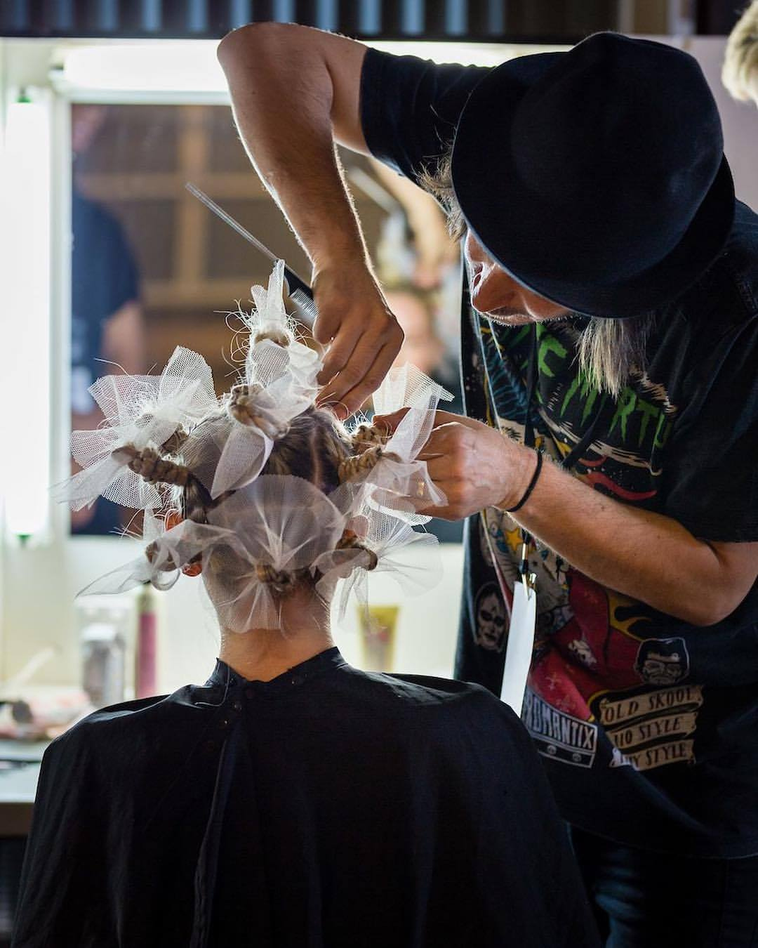 A hairdresser is working on customer to create a beautiful hair design with ribbons.