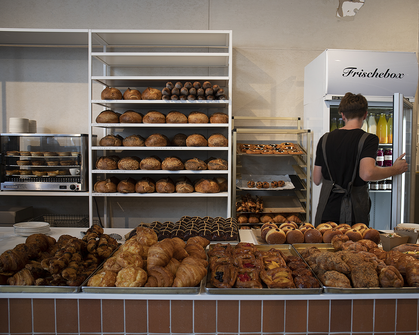 A server dives into the chiller cabinet at Daily Bread with an array of delicious baked goods in the foreground.
