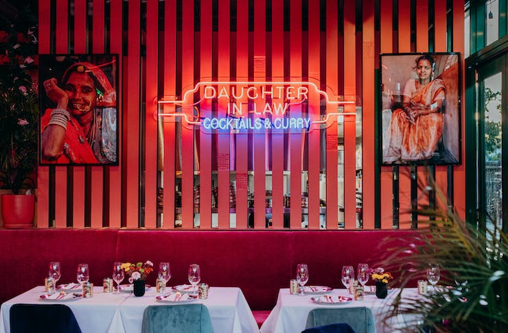 a table setting with a neon sign in the background