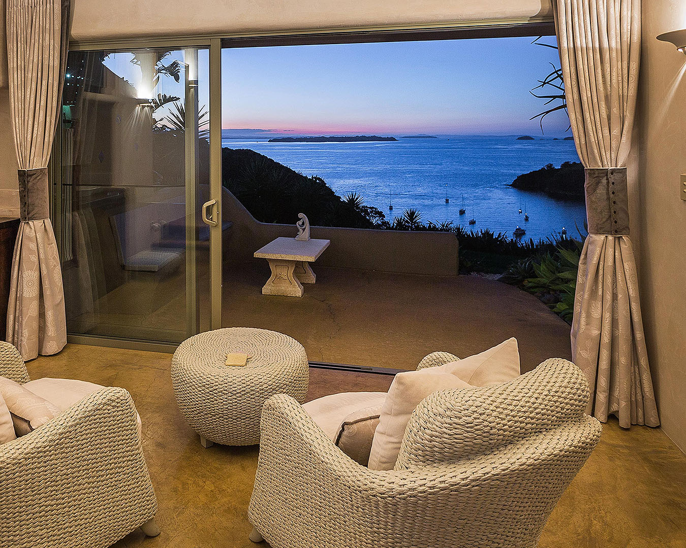 A room looks out on a stunning sunset on Delamore Lodge on Waiheke Island.