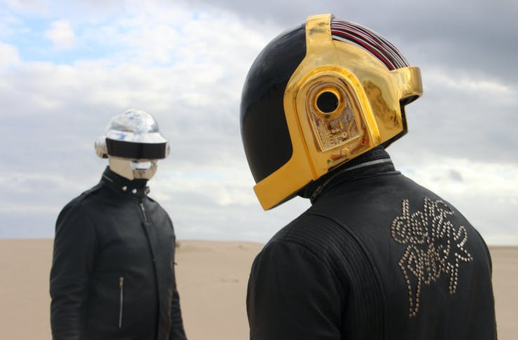 Discovery Tribute Band stand in the desert with helmets on.
