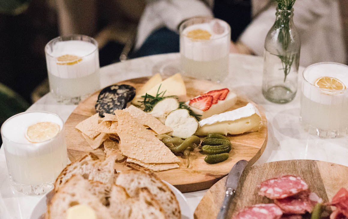 a table filled with gin drinks and cheese boards