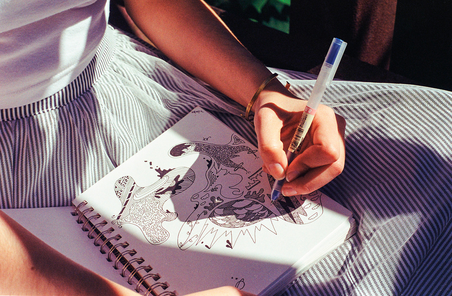 A girl doodles on her notepad on a sunny day.