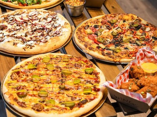 Image of pizzas and wings from Dough Boys