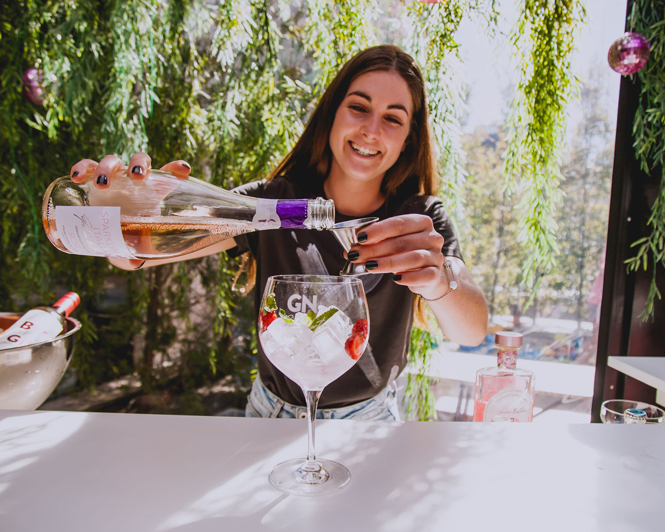 A woman prepares a delicious pink cocktail.