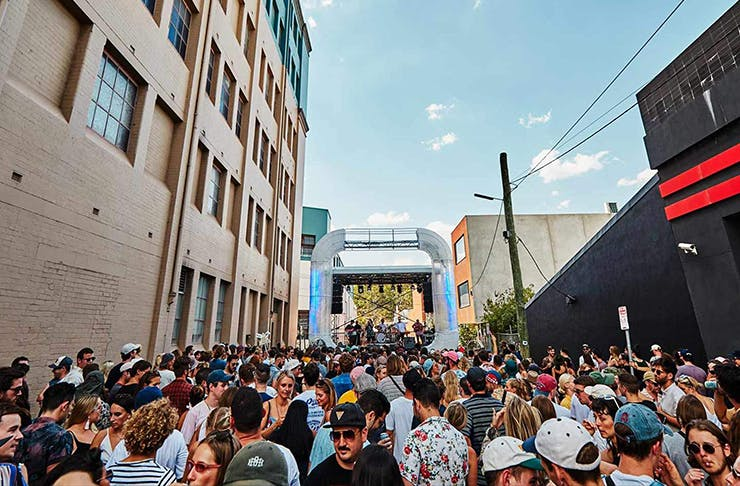 a laneway filled with people dancing in front a stage.
