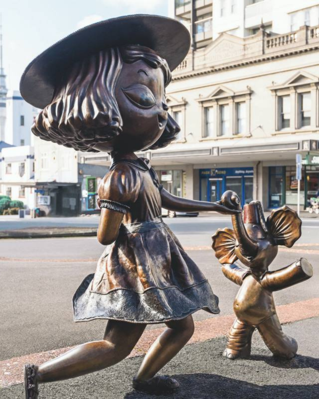 Two small bronze sculptures on Karangahape Road of a girl holding hands with an elephant.