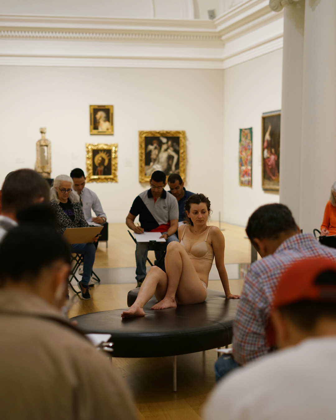 A woman is a still life model as people sit around her sketching at the Auckland Art Gallery