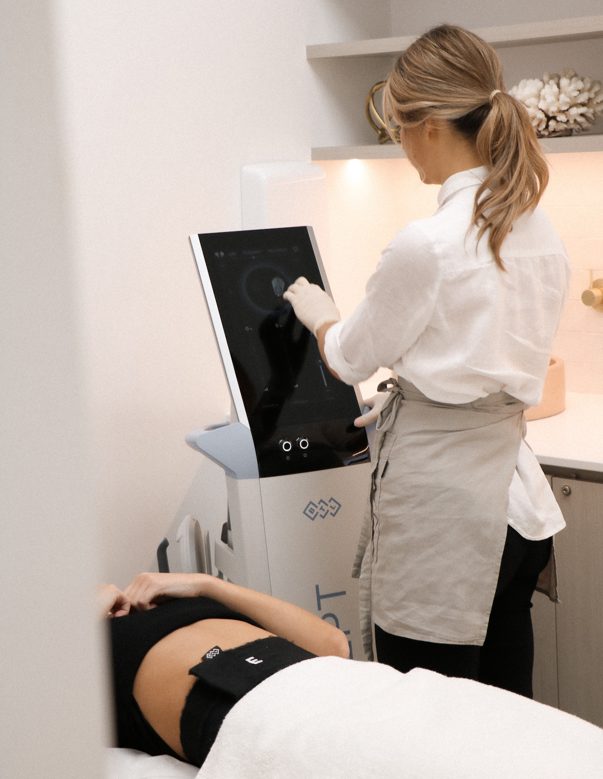 A technician setting up the EMSCULPT treatment for a cient