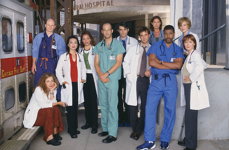 The cast and crew of E.R. stand in an ambulance bay