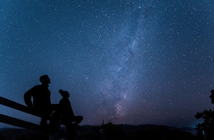 Two people gaze up at the night sky at Eastern Walkway, one of the best stargazing spots  in Wellington.