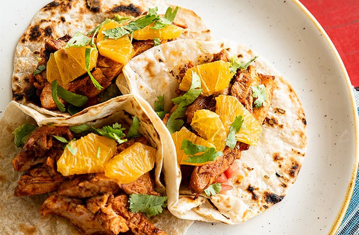 Three soft shell chicken tacos topped with mandarin pieces.