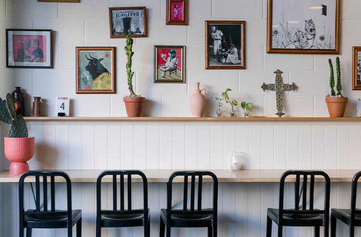 Bar seating underneath a wall of framed prints