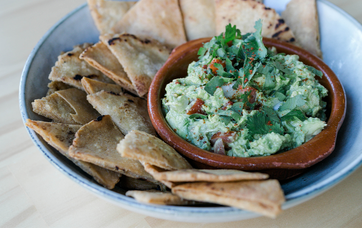 a plate of corn chips and guacamole