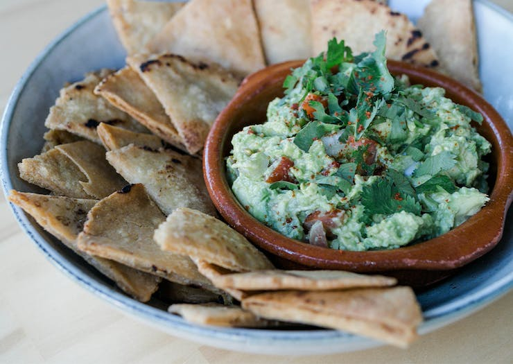 A bowl of guacamole and corn chips
