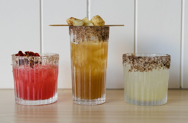 three different cocktails lined up on a bench