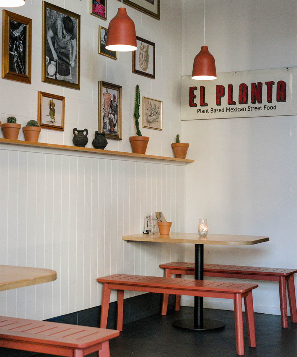 Interior of El Planta, with two red tables along a frame covered wall