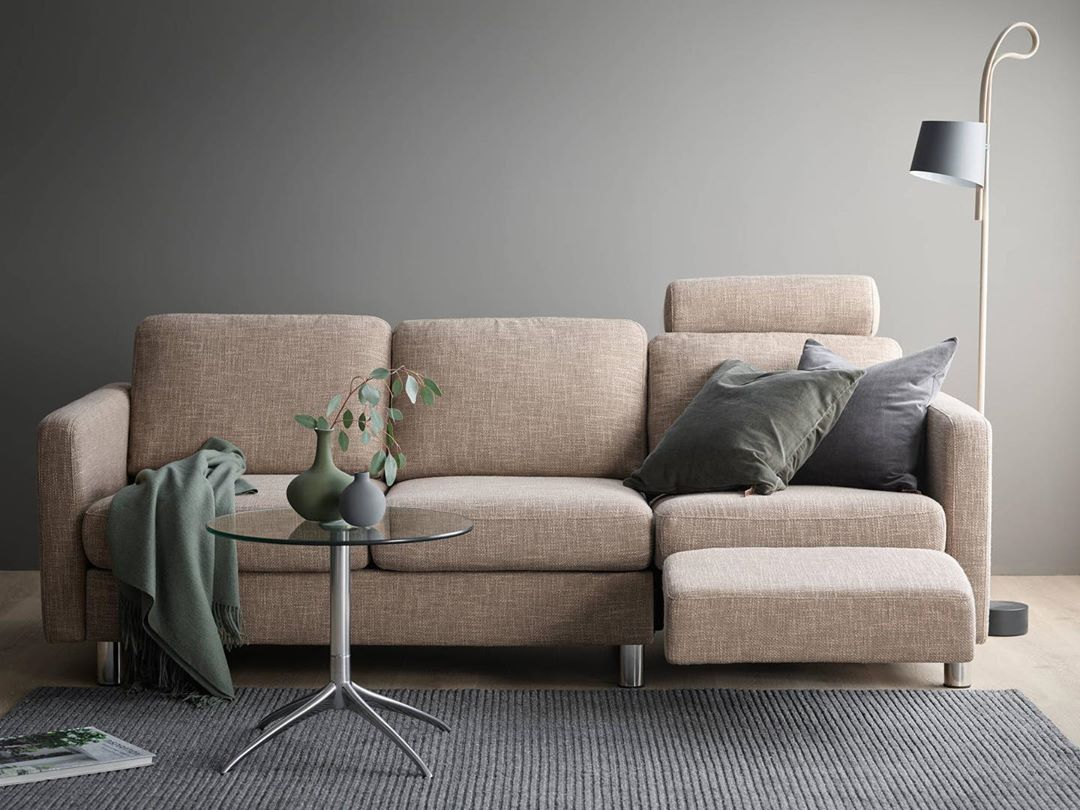 A navy blanket is draped over an oat coloured couch.