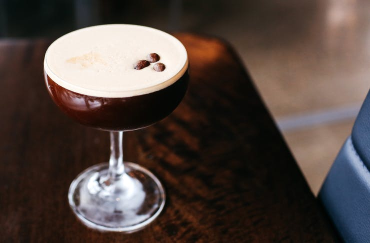 An espresso martini in a glass topped with three coffee beans