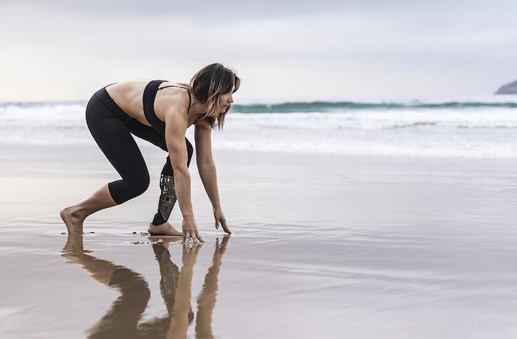 Girl with prosthetic limb on the beach about to start running
