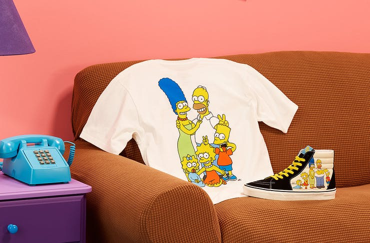 The Simpsons x Vans tshirt and Sk8-hi tops sit on The Simpson's couch.