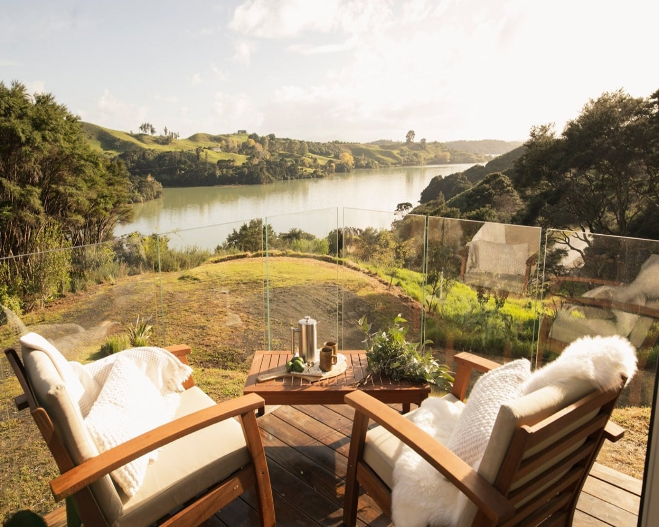 Two cosy chairs at Tarata eco retreat and a coffee pot on a deck overlooking a peaceful-looking harbour.