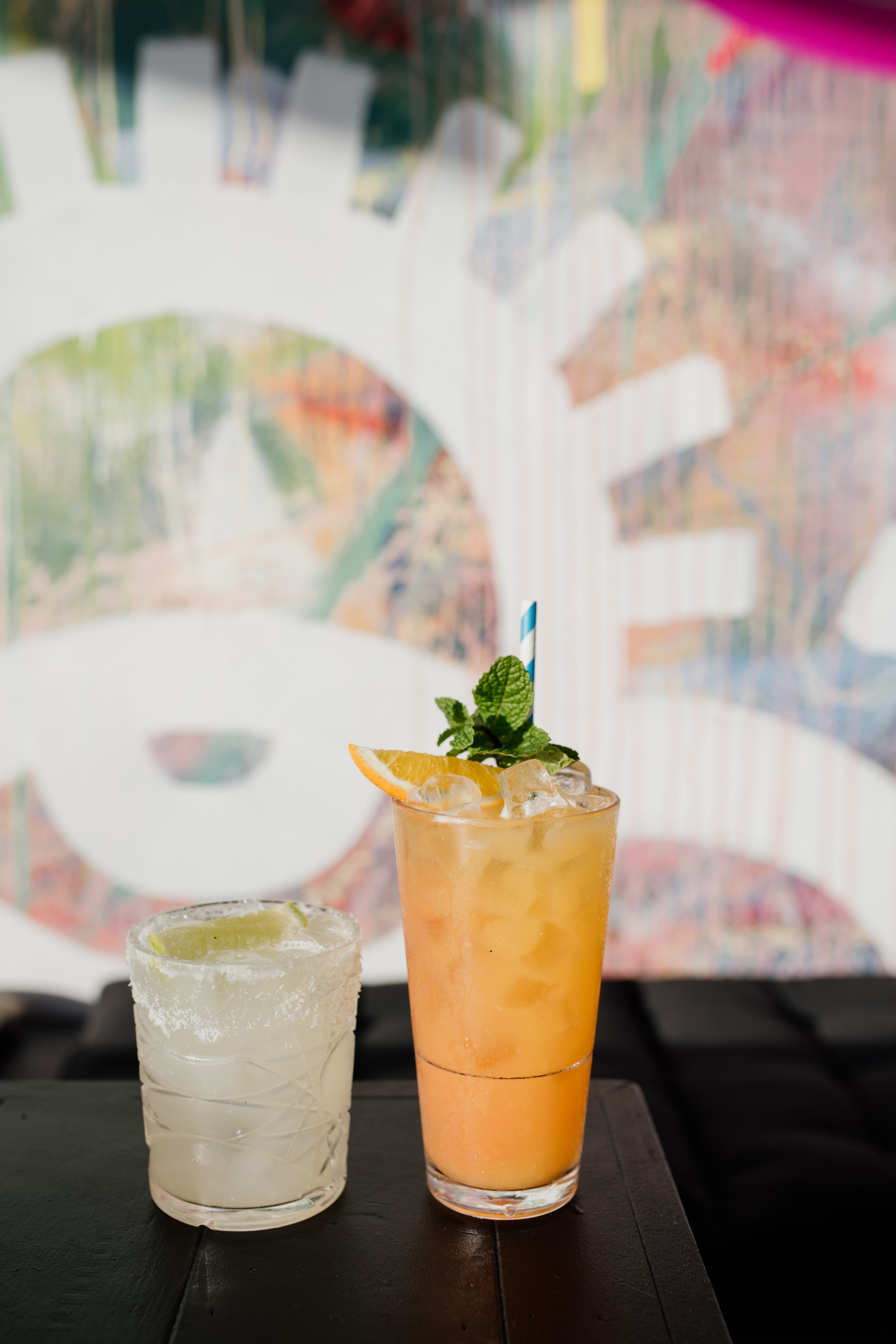 two cocktails against a graffitied wall