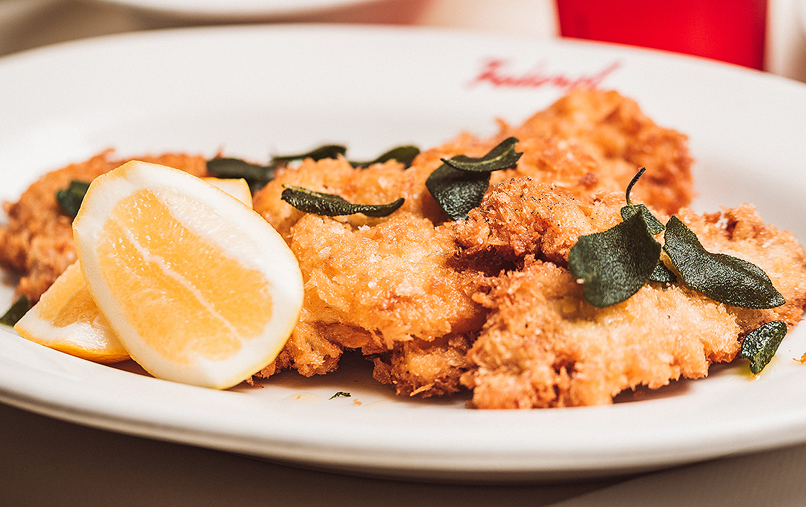 A delicious looking schnitzel from Federal Delicatessen sitting on a plate with crispy sage leaves on top and a slice of lemon.