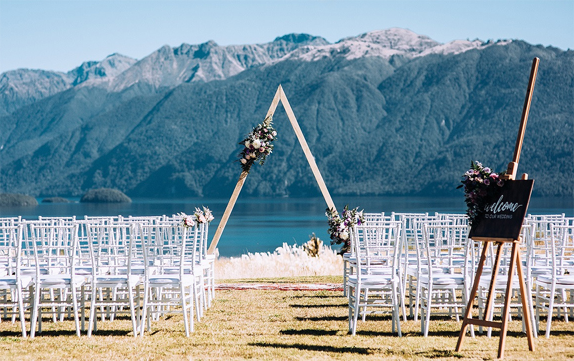 Lines of white chairs and a wedding arch set up at Fiordland Lodge just awaits the bride and groom.
