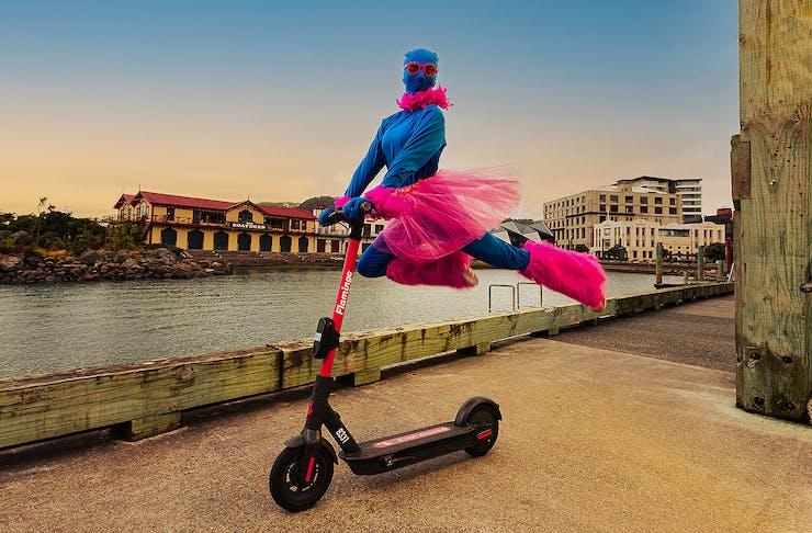 A person dressed in pink and blue leaps on the back of a scooter, cutting a dramatic figure.