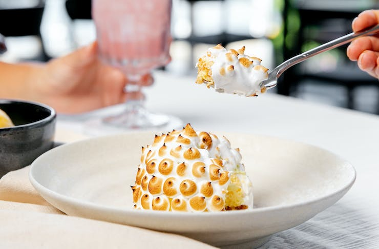 A meringue dessert is scooped onto a spoon.