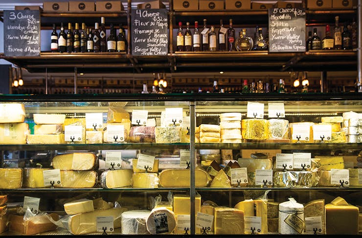 A cheese store with various cheeses on sale on a shelf.