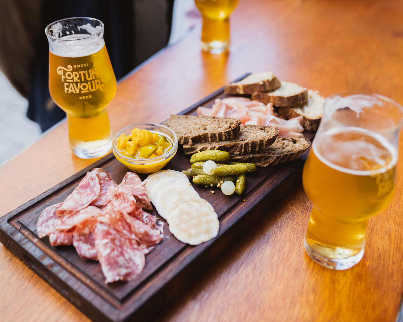 A beautiful graze board with cold cuts, bread and condiments alongside pints of fortune favour beers