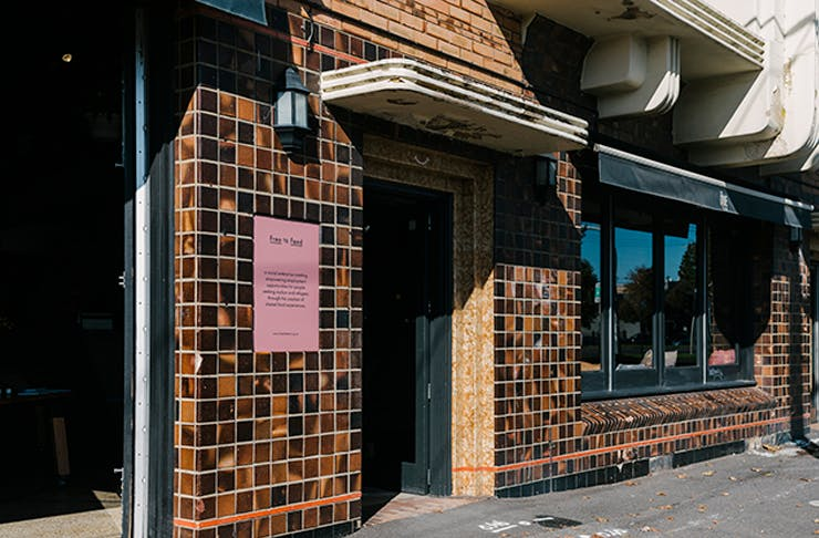 The exterior entrance to Free To Feed with brown tiling and a pink sign.